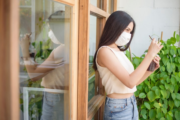 Mulher bonita com máscara facial está segurando café na frente da cafeteria Foto Premium