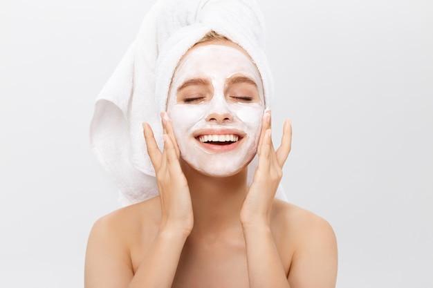 Mulher bonita com máscara facial no fundo branco Foto Premium