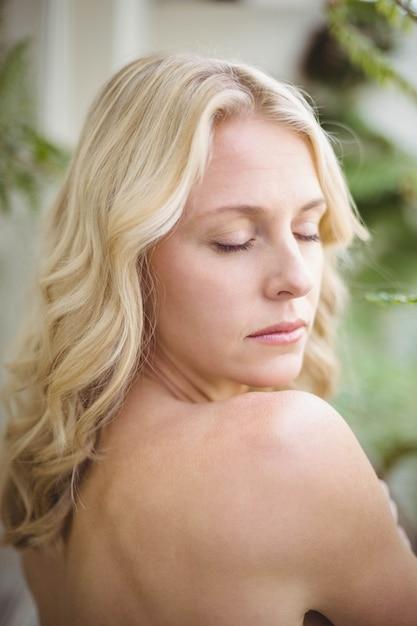 Mulher bonita com os olhos fechados na sala de estar Foto Premium