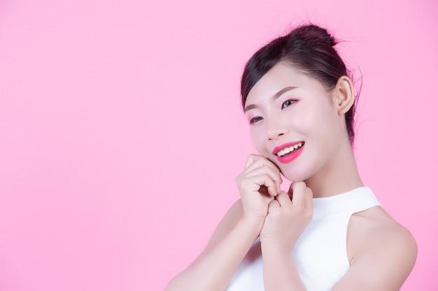 Mulher bonita com pele saudável e beleza em um fundo rosa. Foto gratuita