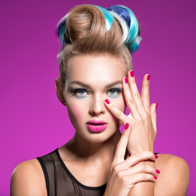 Mulher bonita com penteado fashion e unhas cor de rosa. retrato da moda da jovem modelo caucasiano com maquiagem brilhante. maquiagem da moda. retrato do close up. lindo rosto de uma garota atraente - estúdio. Foto gratuita