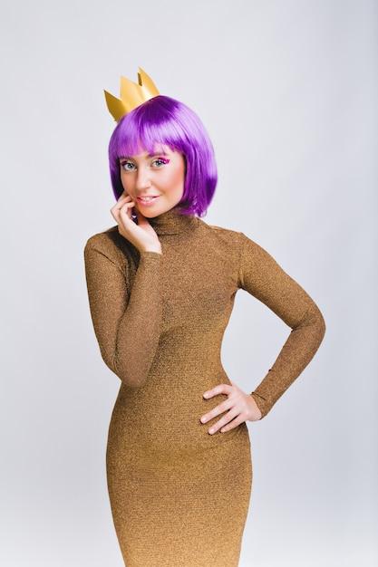 Mulher bonita com penteado violeta em vestido de luxo. ela tem coroa de ouro, sorrindo Foto gratuita