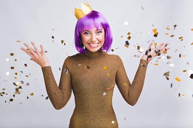 Mulher bonita com penteado violeta se divertindo em enfeites de ouro. ela usa coroa de ouro, sorrindo Foto gratuita
