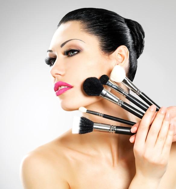 Mulher bonita com pincéis de maquiagem perto de seu rosto. menina bonita posa com ferramentas cosméticas Foto gratuita