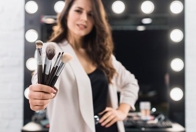Mulher bonita com pincéis na mão Foto gratuita
