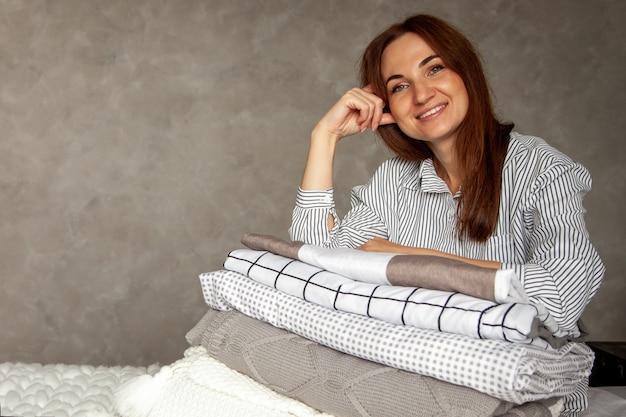 Mulher bonita com robe quente grosso de inverno está sentada e dobrando ordenadamente a roupa de cama e toalhas de banho brancas. organização e classificação da roupa limpa. têxtil de algodão orgânico e natural. fabricação. Foto Premium