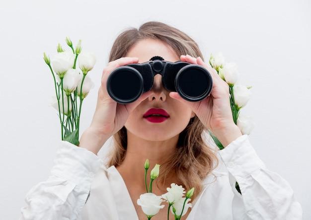 Mulher bonita com rosas brancas em mangas com binóculo Foto Premium