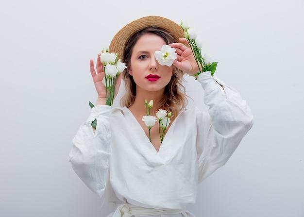 Mulher bonita com rosas brancas em mangas Foto Premium