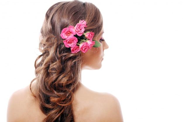 Mulher bonita com rosas no cabelo Foto gratuita