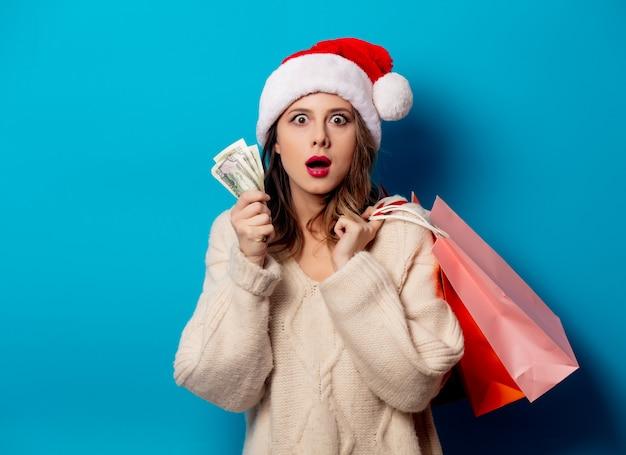 Mulher bonita com sacolas de compras e relógio de dinheiro na parede azul Foto Premium