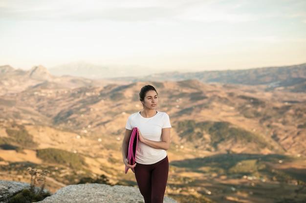 Mulher bonita com tapete de ioga, olhando para longe Foto gratuita