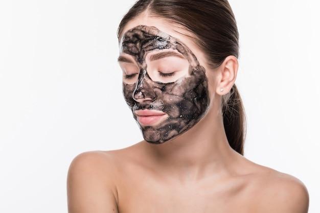Mulher bonita com um barro ou uma máscara de lama no rosto isolado sobre parede branca Foto gratuita