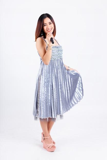 Mulher bonita com um lindo vestido e microfone sem fio Foto gratuita