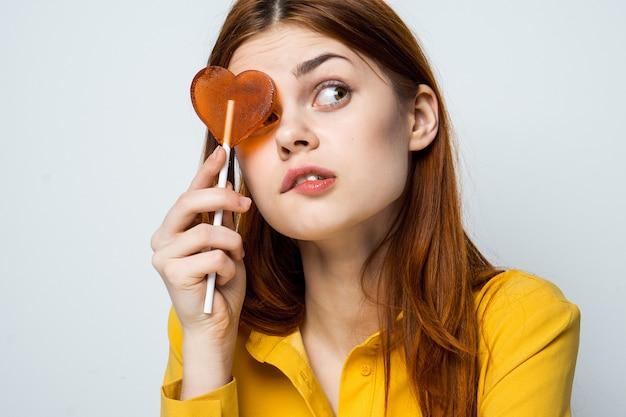 Mulher bonita com um pirulito de coração em uma camisa amarela apresenta emoções diferentes no dia dos namorados Foto Premium