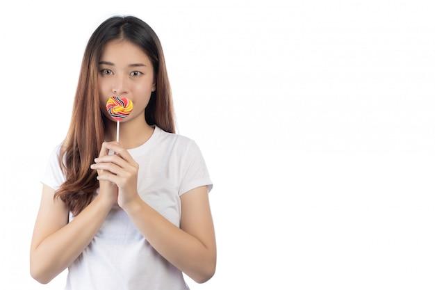 Mulher bonita com um sorriso feliz que guarda uns doces da mão, isolados no fundo branco. Foto gratuita