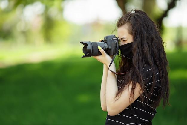 Mulher bonita com uma câmera usa uma máscara médica e tira fotos no parque Foto Premium