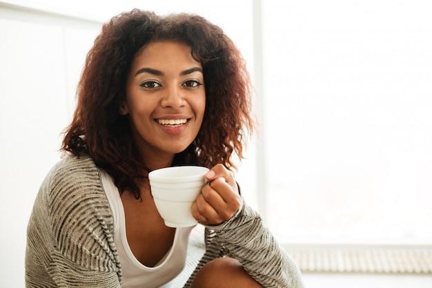 Mulher bonita com uma xícara de chá, sentada no chão Foto gratuita