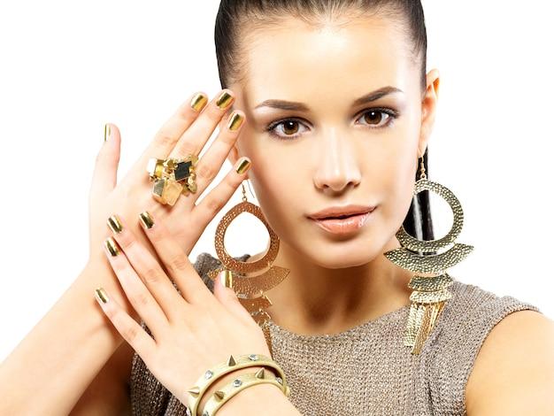 Mulher bonita com unhas de ouro e joias de ouro lindas isoladas na parede branca Foto gratuita
