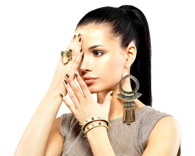 Mulher bonita com unhas douradas e joias de ouro lindas isoladas no branco Foto gratuita