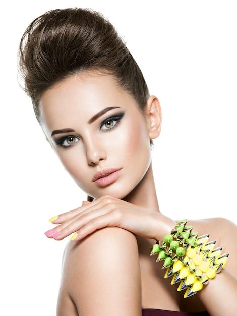 Mulher bonita com unhas multicoloridas e pulseira cravejada à mão Foto gratuita