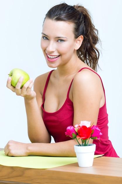 Mulher bonita comendo uma maçã verde Foto gratuita