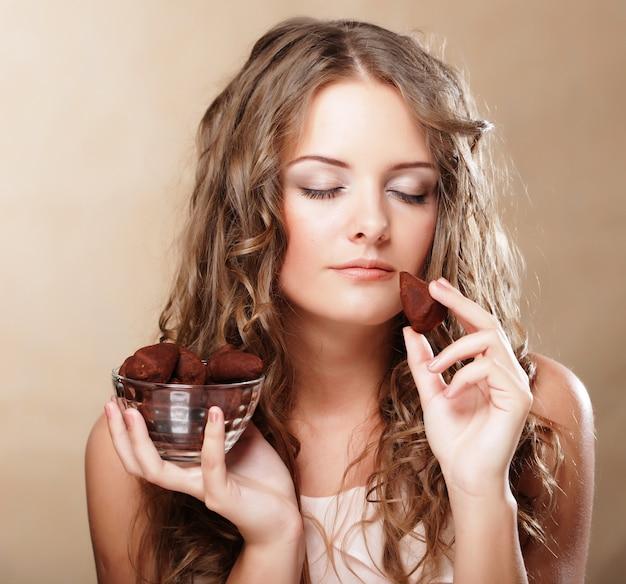Mulher bonita, comer um bombom de chocolate | Foto Premium