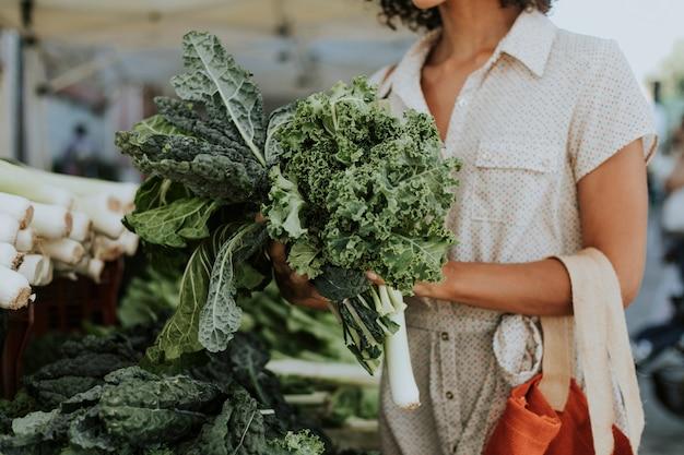 Mulher bonita comprando couve em um mercado de agricultores Foto gratuita