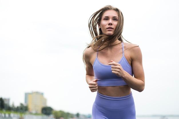 Mulher bonita correndo tiro de ângulo baixo Foto gratuita