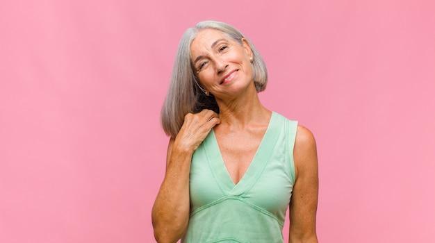 Mulher bonita de meia-idade se sentindo apaixonada, sorrindo, acariciando e se abraçando, permanecendo solteira, sendo egoísta e egocêntrica Foto Premium