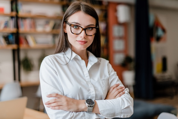 Mulher bonita de óculos e camisa no escritório Foto Premium