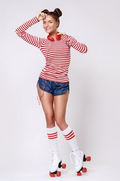 Mulher bonita de patins e com fones de ouvido vermelhos Foto Premium