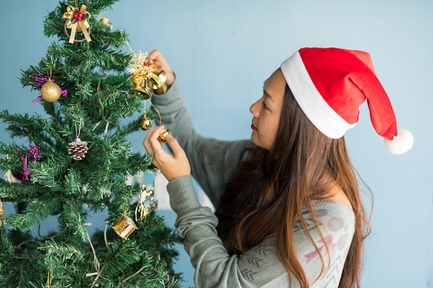 Mulher bonita decorar sinos na árvore de natal Foto Premium