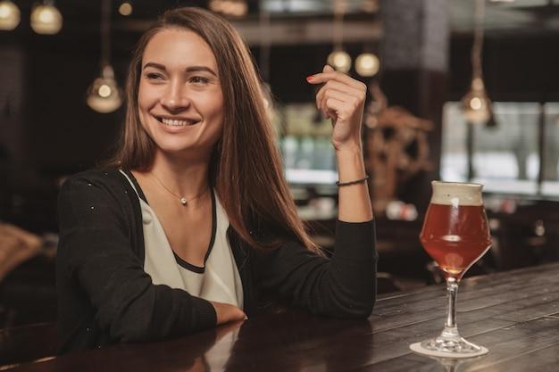Mulher bonita, desfrutando de beber cerveja no pub local Foto Premium