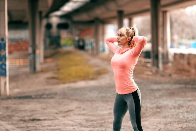 Mulher bonita desportiva loura dedicada com cara séria que exercita ao ar livre. vista lateral. Foto Premium