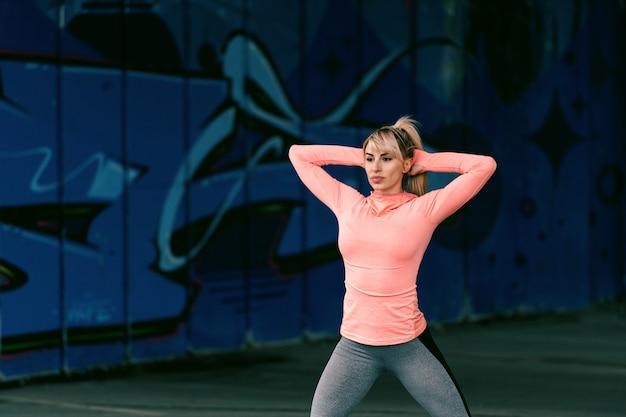 Mulher bonita desportiva loura dedicada com cara séria que exercita ao ar livre. Foto Premium
