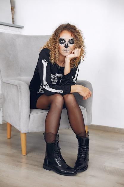Mulher bonita do crânio de maquiagem de halloween com penteado loiro. menina modelo santa muerte em traje preto. Foto gratuita