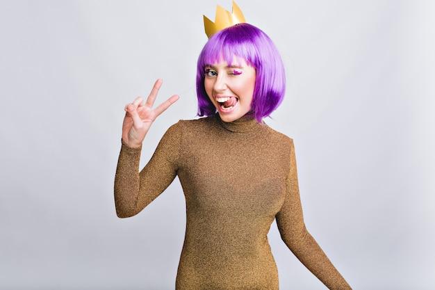 Mulher bonita do retrato com coroa de ouro se divertindo. ela usa corte de cabelo violeta, mostra língua e parece feliz Foto gratuita
