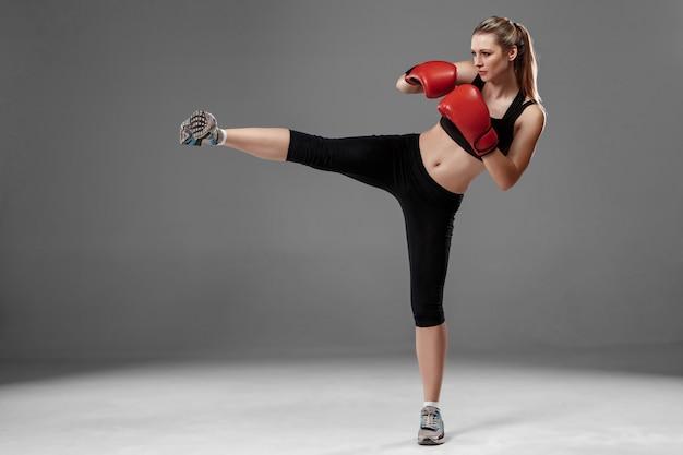 Mulher bonita é boxe em fundo cinza Foto gratuita