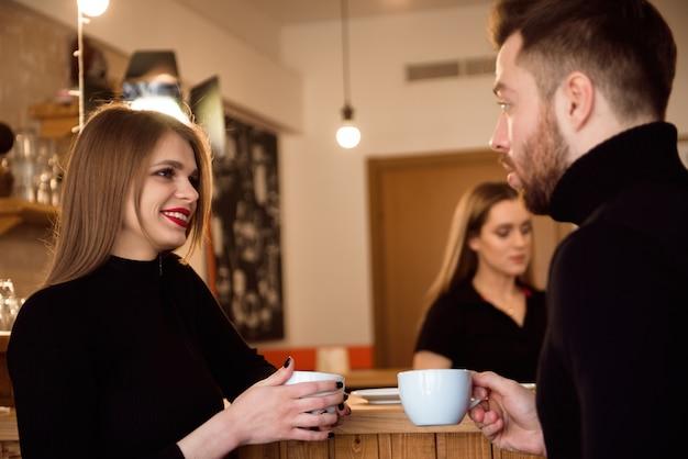 Mulher bonita e café bebendo do homem considerável ao passar o tempo na cafetaria. Foto Premium