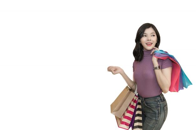 Mulher bonita é fazer compras no shopping usando o cartão de crédito. mulher de óculos e segurando o saco de compras de moda Foto Premium