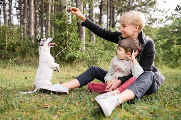 Mulher bonita e menino brincando com cachorro Foto gratuita