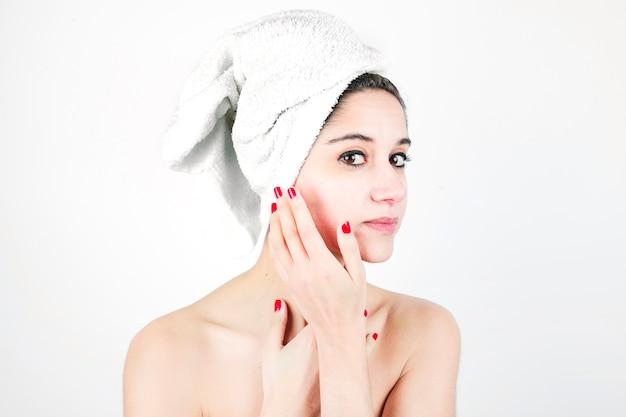 Mulher bonita e natural jovem envolto em toalha isolada sobre fundo branco Foto gratuita