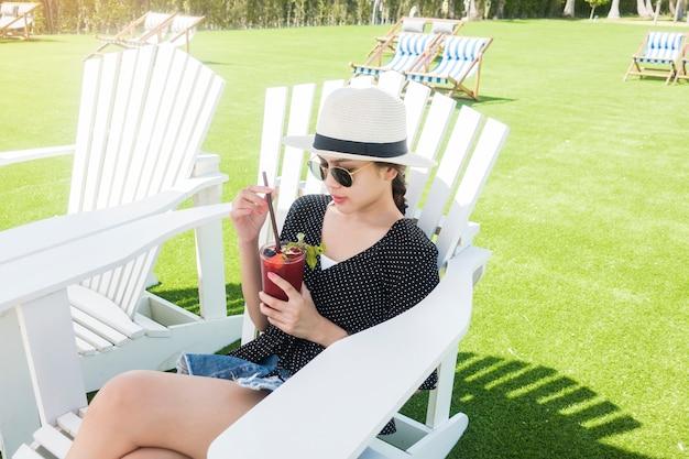 Mulher bonita é relaxante na praia, sob o guarda-chuva Foto Premium