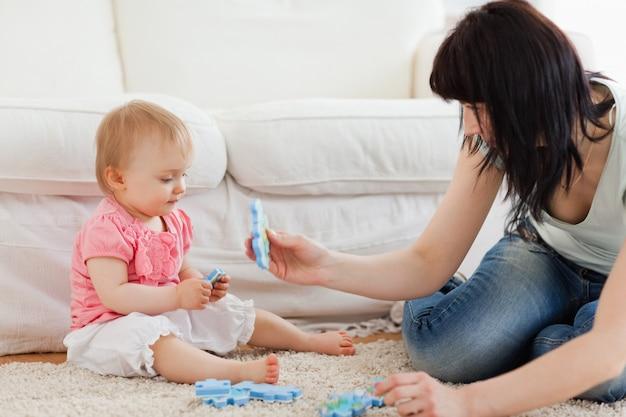 Mulher bonita e seu bebê brincando com peças de quebra-cabeça enquanto está sentado em um tapete Foto Premium