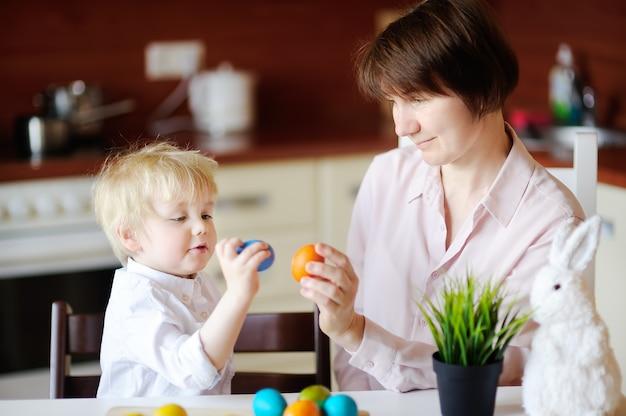 Mulher bonita e seu lindo filho ou neto brincando com ovo de páscoa no dia de páscoa Foto Premium