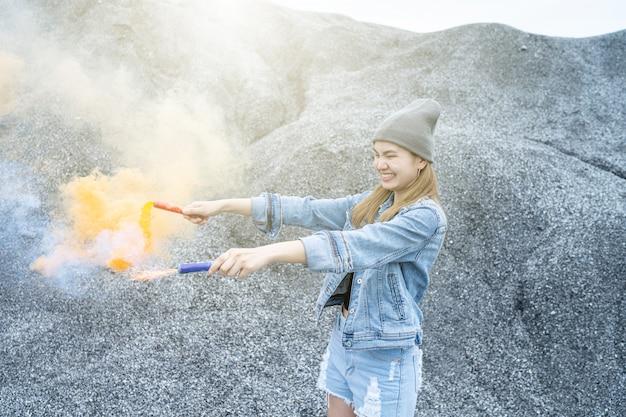 Mulher bonita ela está jogando uma cor de fumaça de fogos de artifício no lugar do rock grand canyon Foto Premium