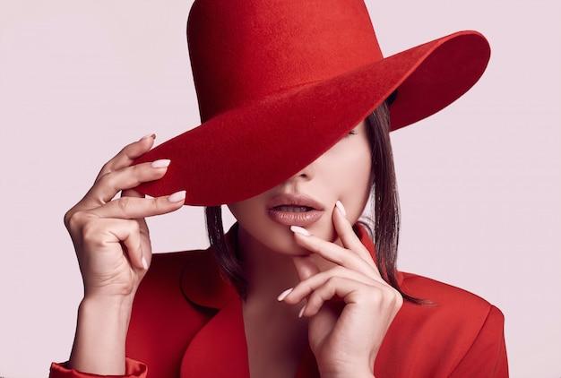 Mulher bonita elegante em um terno vermelho elegante e chapéu largo Foto Premium