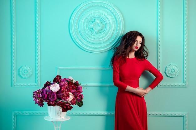 Mulher bonita elegante sexy perto verde parede decorada. buquê de flores. vestido vermelho. Foto Premium