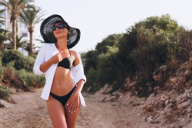 Mulher bonita em biquíni e camisa por palmas Foto gratuita