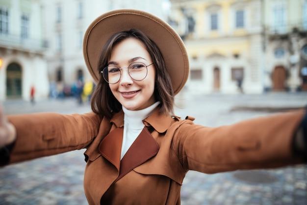 Mulher bonita em copos leva selfie enquanto segura o telefone na cidade Foto gratuita
